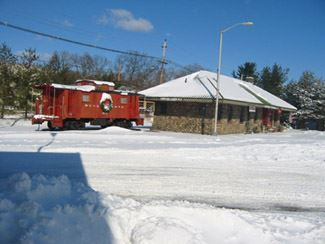Train Station from afar with a caboose, with snow on the ground