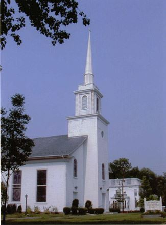Image of the white Pompton Lake Reformed Church, with a steeple, and sign out front, with a yard