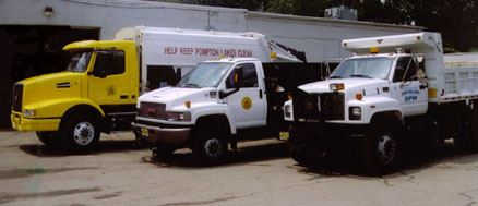 Image of three public works trucks in a staggered line
